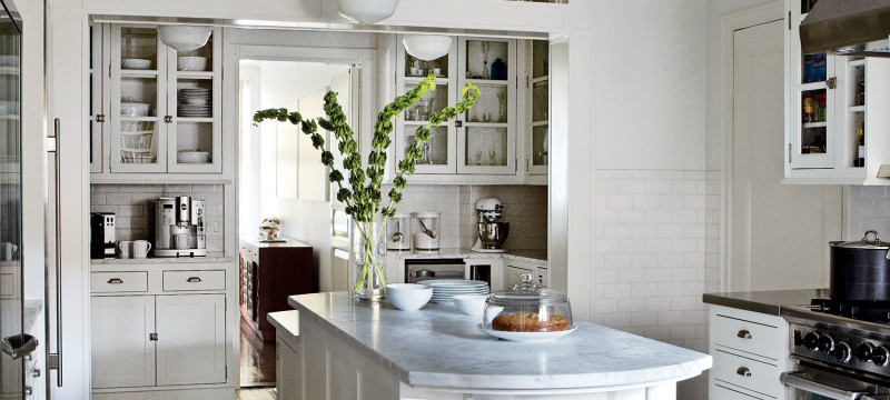 Tracy Pollan and Michael J. Fox's New York City kitchen, designed by Gomez Associates Inc., features classic schoolhouse light fixtures, Shaker-style cabinetry, and stainless-steel and marble countertops.