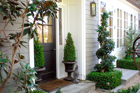 A pair of boxwoods in planters on either side of the front door is a  traditional