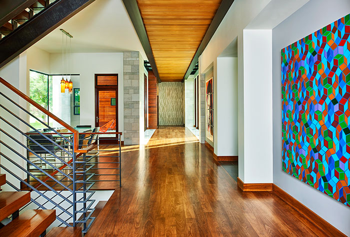 The first-floor hallway leads to a large hidden mudroom.  The geometric painting is Quantum Zone by Colorado artist Clark Richert.