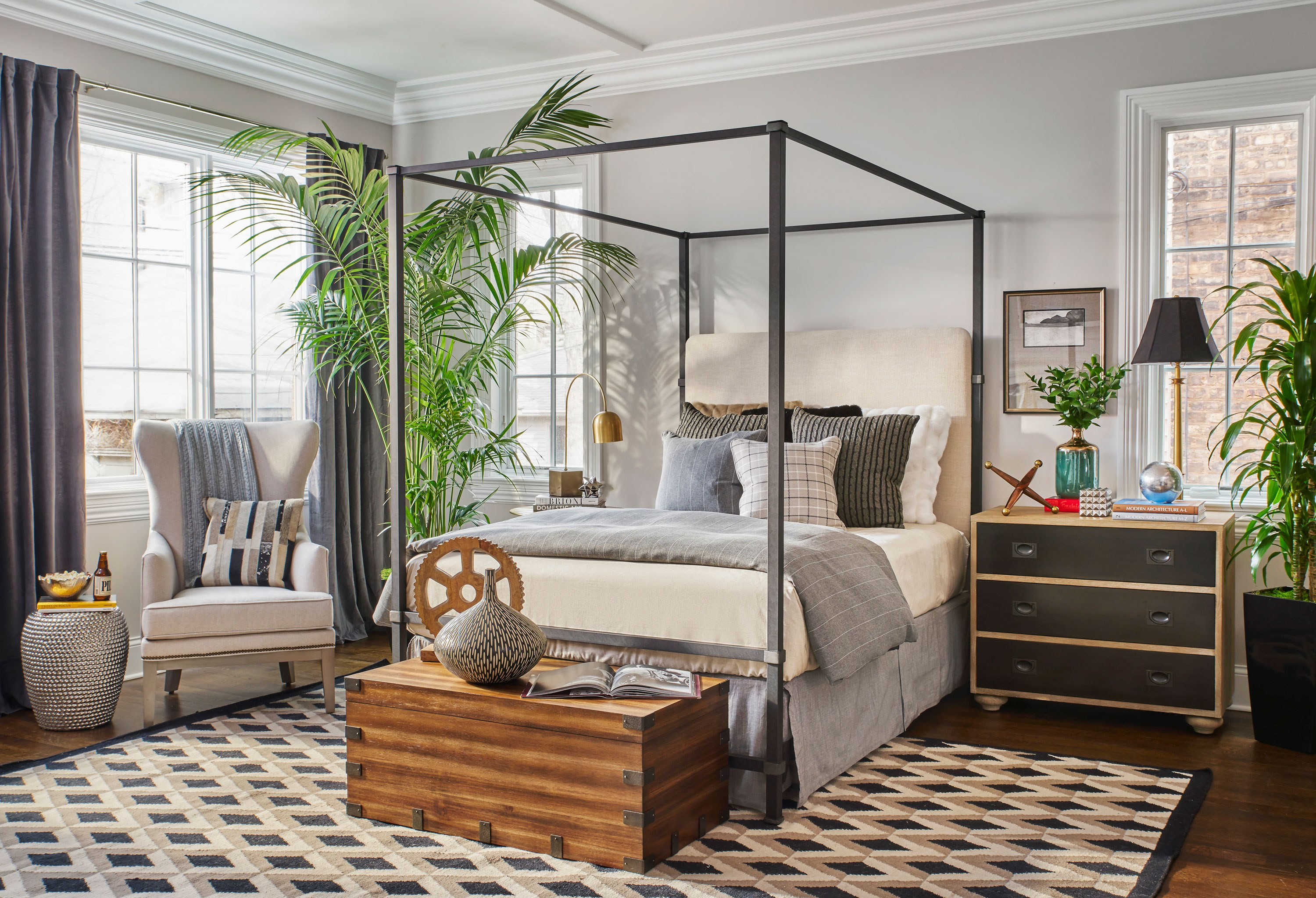 """Matching furniture sets can be boring and unimaginative. I intentionally mismatch pieces for visual diversity. In this bedroom, I balanced a heavy bedside table with a tall tree and accent chair for symmetry. The high ceilings were prone to shrink most beds, but we chose a tall iron canopy bed that fit the space perfectly."""