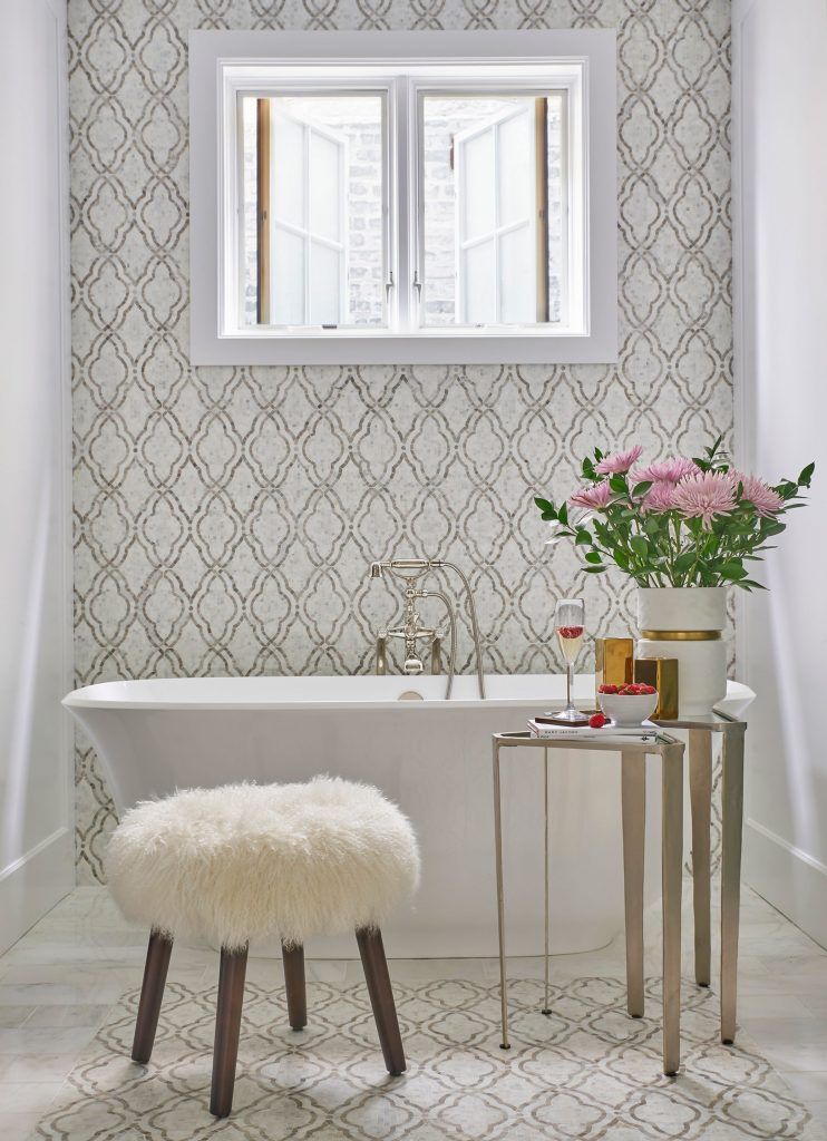 """Bathrooms often feel cold and disconnected from the public rooms. Add furniture such as an accent table, a cozy chair, or an ottoman to bring warmth and comfort."""
