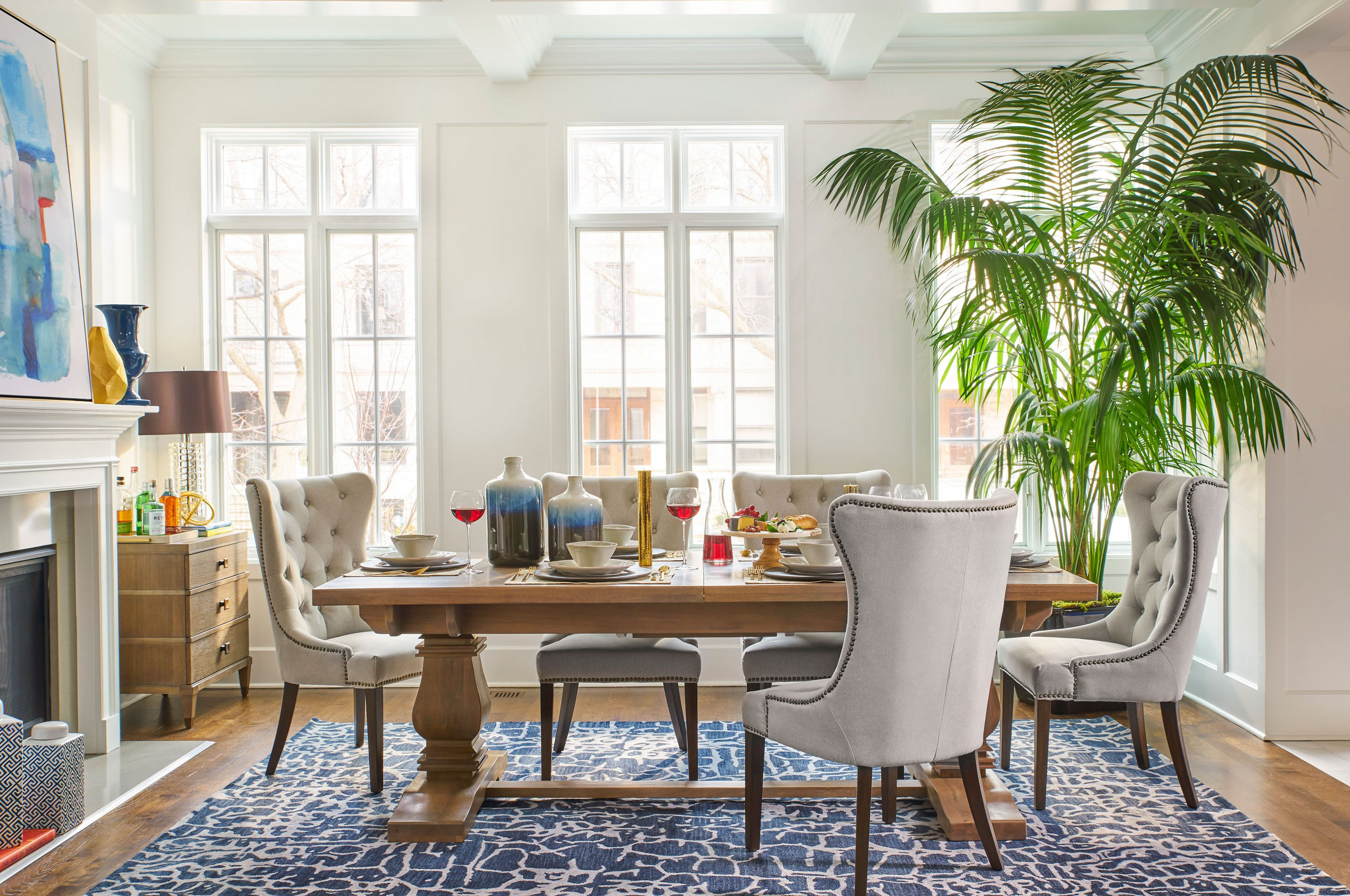 """For a more casual vibe, choose a lighter finish for your dining table and pair it with soft upholstered chairs and a bright patterned rug. I like to accessorize the dining room table and incorporate plants or flowers. As a result, your dining room will look less stuffy and more lived in—in a good way."""
