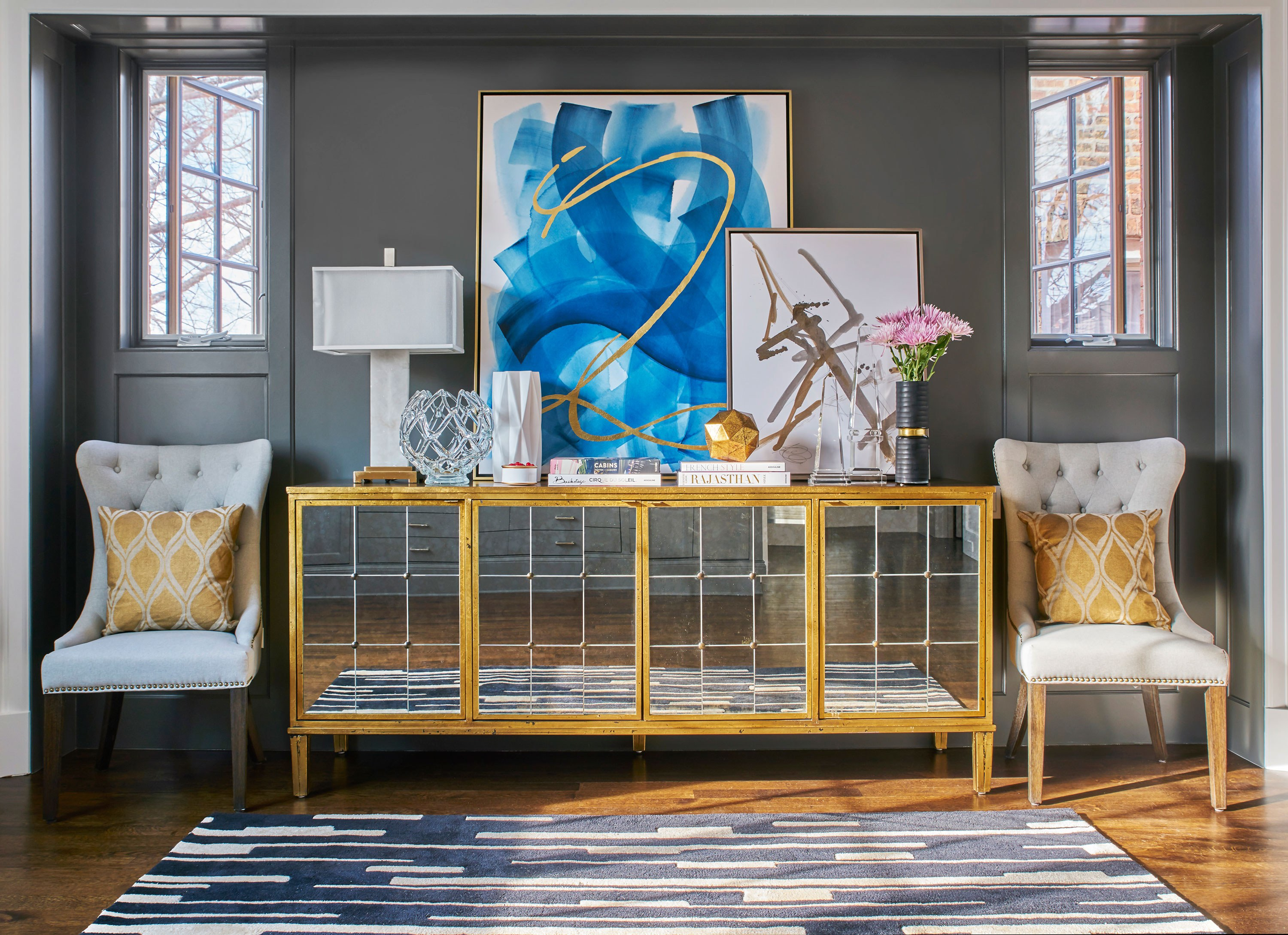 """In a dark space, try integrating reflective furniture and accessories. Next, mix in light colored art, upholstery pieces, and rugs. Everything will feel light, bright, and more spacious."""
