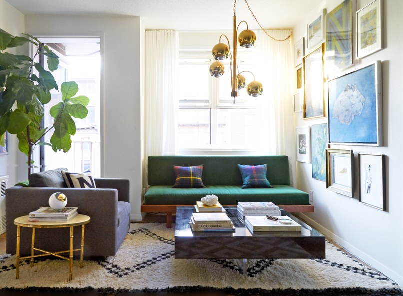 A Moroccan rug anchors the living area, which features a vintage brass Arc light fixture, a Jonathan Adler lacquer block cocktail table, and a midcentury daybed upholstered in velvet.