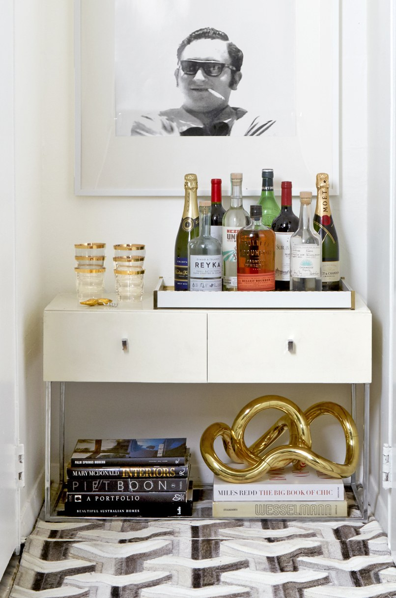 "In a nook between the closet and bath, Obeid installed a bar area that's topped with a framed image of his late father. ""It's the perfect place to raise a glass to him,"" says Obeid."